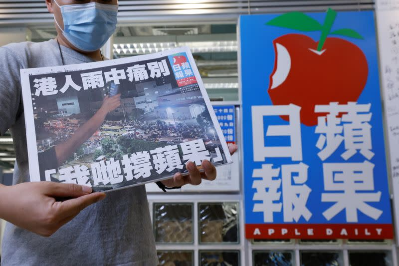 A staff member of Apple Daily poses with his final edition of Apple Daily at its headquarters in Hong Kong