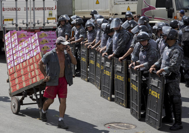 A man pulls a cart of boxed fruit past a cordon of riot police standing guard at the CEAGESP complex, the largest food market in Latin America, in Sao Paulo, Brazil, March 14, 2014. Earlier truck drivers protesting a hike in parking fares at the complex, set vehicles on fire and damaged parking ticket booths. (AP Photo/Andre Penner)