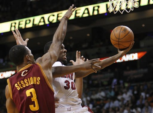 Miami Heat's Norris Cole (30) shoots as Cleveland Cavaliers' Ramon Sessions (3) defends during the first half of an NBA basketball game, Tuesday, Jan. 24, 2012, in Miami. (AP Photo/Lynne Sladky)