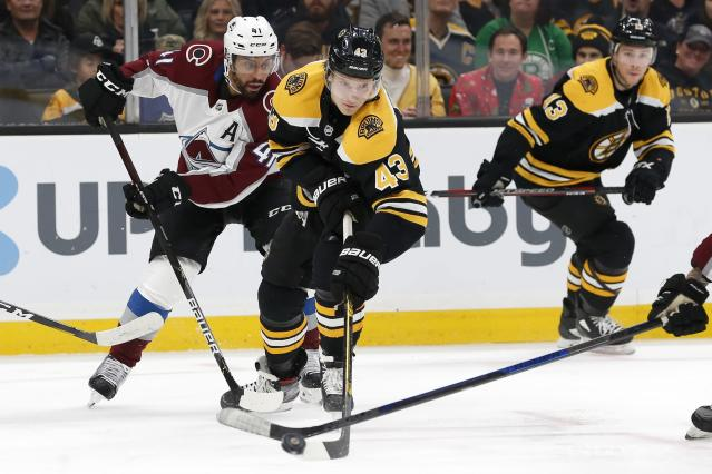 Colorado Avalanche's Pierre-Edouard Bellemare (41) watches as a teammate, out of frame at right, and Boston Bruins' Danton Heinen (43) reach for the puck during the first period of an NHL hockey game in Boston, Saturday, Dec. 7, 2019. (AP Photo/Michael Dwyer)