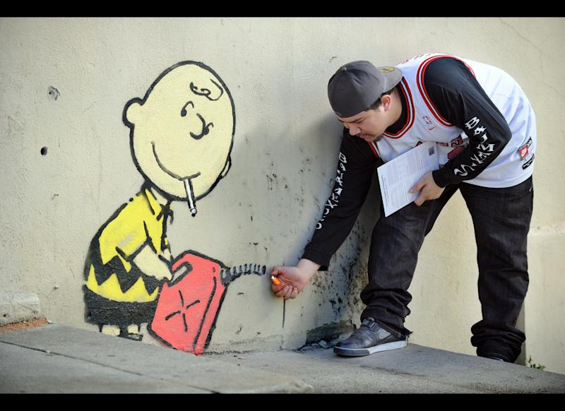 A graffiti attributed to secretive British artist Banksy depicting Charlie Brown figure starting a fire on the side of a burned-out building on Sunset Boulevard in Los Angeles, California on February 17, 2011. An other graffiti was ripped down in Hollywood, amid sightings of other pieces in a reported pre-Oscars publicity stunt in LA. Banksy is nominated for best documentary for 'Exit Through the Gift Shop' at the Oscars, due to be announced on February 27 at the climax of Tinseltown's annual awards season. AFP PHOTO / GABRIEL BOUYS (Photo credit should read GABRIEL BOUYS/AFP/Getty Images)