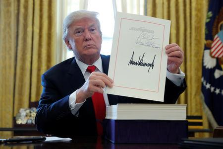 FILE PHOTO: U.S. President Trump displays signbature after signing tax bill into law at the White House in Washington