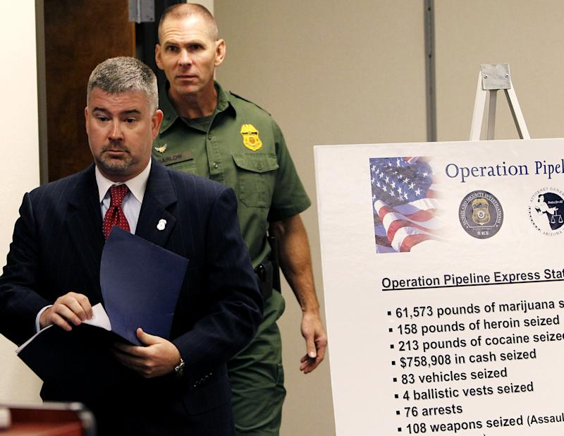 """Matthew Allen, left, special agent in charge of Homeland Security Investigations in Arizona, is joined by Richard Barlow, Acting Chief Patrol Agent for the U.S. Border Patrol, as they arrive with others for a news conference as a variety of multi-jurisdictional law enforcement agencies announce a bust on a major drug smuggling ring in Arizona, Monday, Oct. 31, 2011, in Phoenix.  Operation """"Pipeline Express"""" has netted 76 arrested, has seized 61,573 pounds of marijuana, 213 pounds of cocaine, 158 of heroin, $758,908 in cash, 83 vehicles, 108 weapons, and four ballistic vests, all linked, according to law enforcement, to a faction of the Sinaloa Cartel based in Sonoyta, Sonora, Mexico. (AP Photo/Ross D. Franklin)"""