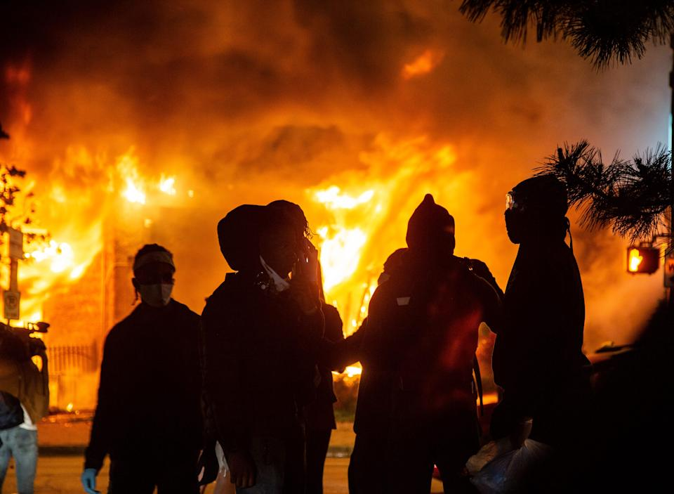 Protestors watch a building burn on Lake St. in Minneapolis Friday, May 29, 2020. Protests continued around the city following the death of George Floyd, a black man who died in police custody. (Via OlyDrop)