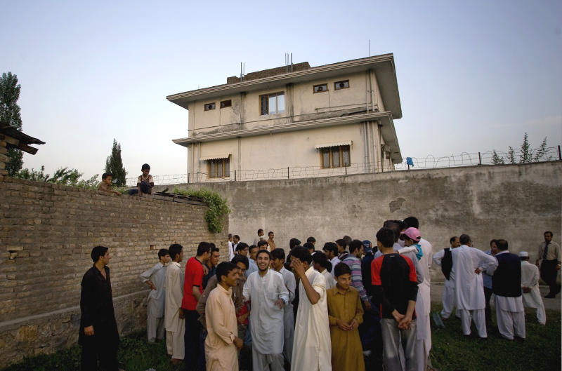 FILE - In this May 3, 2011 file photo, local residents gather outside a house, where al-Qaida leader Osama bin Laden was caught and killed in Abbottabad, Pakistan. Local residents say Pakistan has started to demolish the compound in the northwest city of Abbottabad where Osama bin Laden lived for years and was killed by U.S. commandos. Two residents say the government brought in three mechanized backhoes Saturday, Feb. 25, 2012, and began destroying the tall outer walls of the compound after sunset. They set up floodlights to carry out the work. (AP Photo/B.K.Bangash,File)