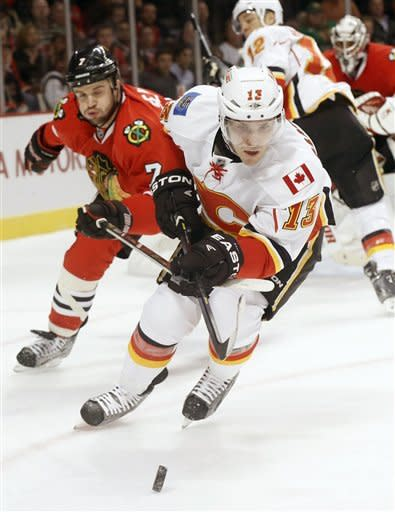 Calgary Flames left wing Mike Cammalleri (13) and Chicago Blackhawks defenseman Brent Seabrook (7) chase after a loose puck during the first period of an NHL hockey game Tuesday, March 26, 2013 in Chicago. (AP Photo/Charles Rex Arbogast)