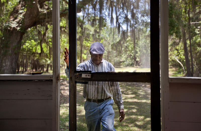 """Stephen Wilson, 68, walks onto the front porch of his home that his father built in the Hog Hammock community of Sapelo Island, Ga. on Wednesday, May 15, 2013. """"Dad built this house with his labor. Every time I put the key in the door, I remember coming home as a child saying, 'Hi, papa. Hi, mama.' It has a lot of remembrance."""" Wilson is one of roughly 47 residents, most of them descendants of West African slaves known as Geechee, who remain on the coastal Georgia island where their ancestors were brought to work a plantation in the early 1800s. Isolated over time to the Southeast's barrier islands, the Geechee of Georgia and Florida, otherwise known as Gullah in the Carolinas, have retained their African traditions more than other African American communities in the U.S. Once freed, the slaves were able to acquire land and created settlements on the island, of which only the tiny 464-acre Hog Hammock community still exists. Eight children catch a ferry every morning to attend school on the mainland since the last school operating on the island closed in 1978. Residents say a sudden tax hike, lack of jobs, and development is endangering one of the last remaining Geechee communities from Florida to North Carolina. (AP Photo/David Goldman) PART OF A 35-PICTURE ESSAY BY DAVID GOLDMAN"""