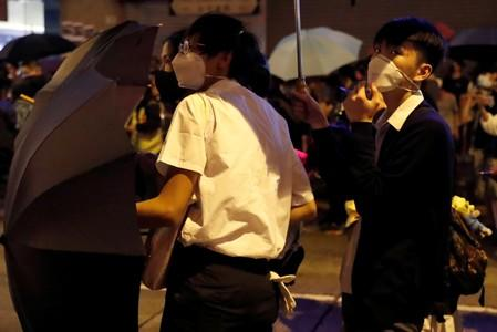 Secondary school students wearing school uniforms attend an anti-extradition bill protest outside Mong Kok police station, in Hong Kong