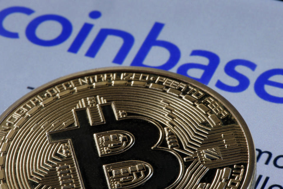 PARIS, FRANCE - APRIL 12: In this photo illustration, a visual representation of the digital Cryptocurrency, Bitcoin, is displayed in front of the home page of the Coinbase cryptocurrency exchange website on April 12, 2021 in Paris, France. Coinbase, America's leading cryptocurrency exchange, arrives on Wall Street on Wednesday April 14 as part of a 'direct introduction'. An IPO, eagerly awaited by crypto enthusiasts, which could value the Californian company at more than 100 billion dollars. Taking advantage of exploding demand for digital currencies, Coinbase said last week that it expects to make a profit of $730 million to $800 million in the first quarter of 2021, more than double the total profit in 2020. Revenues for the first three months of 2021 have likely exceeded last year's, to nearly $1.8 billion. (Photo by Chesnot/Getty Images)
