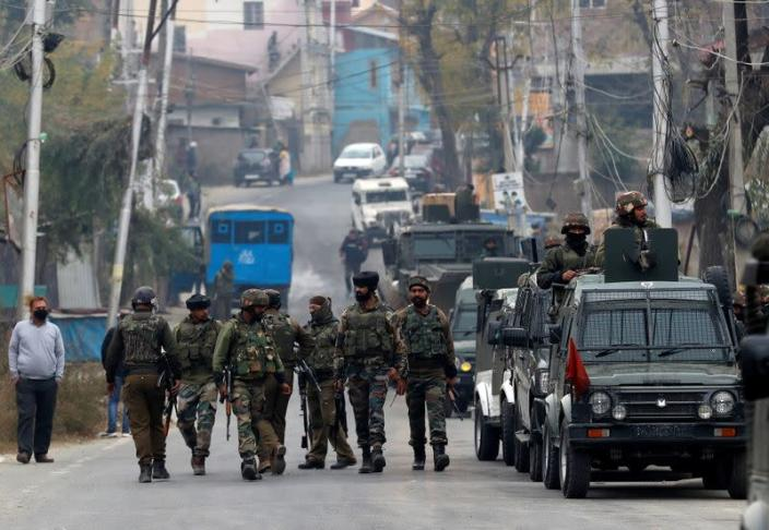 Indian soldiers leave a gun battle site after a suspected militant commander was killed in a gun battle between Indian security forces and suspected militants, at Rangreth