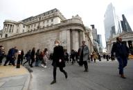 FILE PHOTO: FILE PHOTO: A woman wearing a protective face mask, following an outbreak of the coronavirus, walks in front of the Bank of England in London