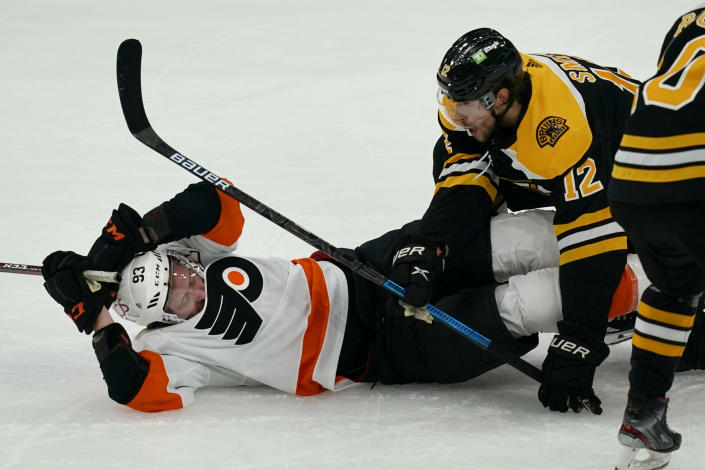 Boston Bruins right wing Craig Smith (12) takes down Philadelphia Flyers right wing Jakub Voracek (93) during the first period of an NHL hockey game Thursday, Jan. 21, 2021, in Boston. (AP Photo/Elise Amendola)