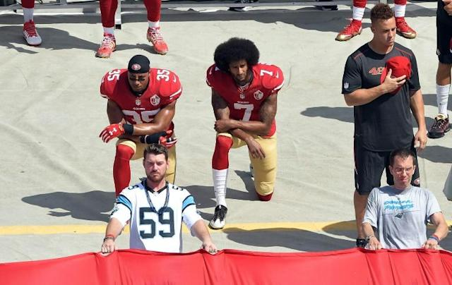 Colin Kaepernick #7 and Eric Reid #35 of the San Francisco 49ers kneel during the national anthem before their game against the Carolina Panthers at Bank of America Stadium on September 18, 2016 in Charlotte, North Carolina (AFP Photo/GRANT HALVERSON)