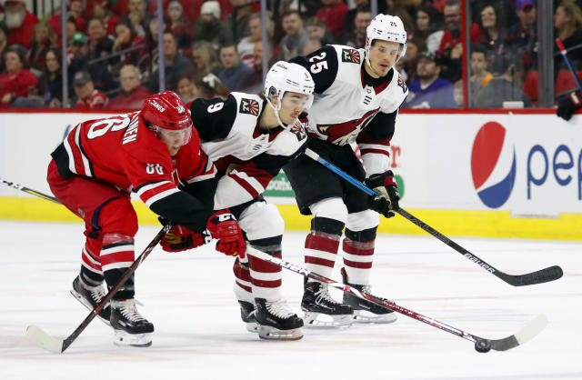 Carolina Hurricanes' Teuvo Teravainen (86) tips the puck away from Arizona Coyotes' Clayton Keller (9) with Coyotes' Nick Cousins (25) looking on during the first period of an NHL hockey game, Sunday, Dec. 16, 2018, in Raleigh, N.C. (AP Photo/Karl B DeBlaker)