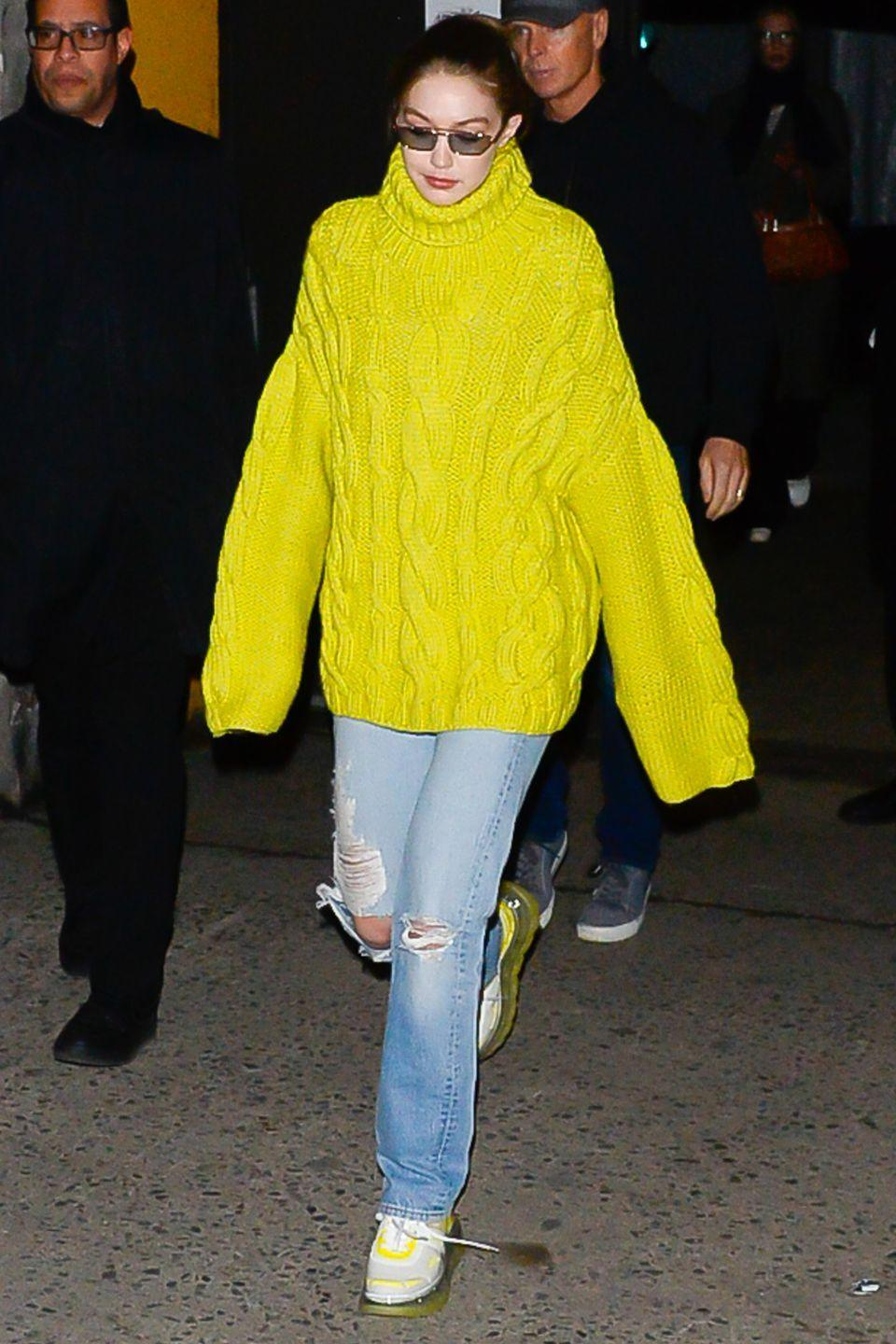 <p>In an oversized chartreuse sweater, light-wash distressed jeans, and white and chartreuse sneakers.</p>