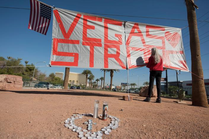 <p>Las Vegas resident Nancy Cooley writes a message at a makeshift memorial to victims of the Las Vegas mass shooting, Oct. 5, 2017 at the iconic Welcome To Fabulous Las Vegas sign, in Las Vegas, Nev. (Photo: Robyn Beck/AFP/Getty Images) </p>