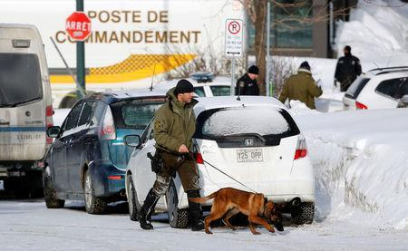 """Police officers patrol the perimeter at the scene of a fatal shooting at the Quebec Islamic Cultural Centre in Quebec City, Canada. Six people were killed and eight wounded when gunmen opened fire at a Quebec City mosque during Sunday night prayers, in what Canadian Prime Minister Justin Trudeau called a """"terrorist attack on Muslims"""". REUTERS/Mathieu Belanger"""
