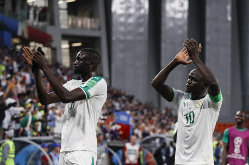 Senegal's Cheikhou Kouyate, left, and Sadio Mane greet supporters at the end of the group H match between Japan and Senegal at the 2018 soccer World Cup at the Yekaterinburg Arena in Yekaterinburg , Russia, Sunday, June 24, 2018. (AP Photo/Eugene Hoshiko)