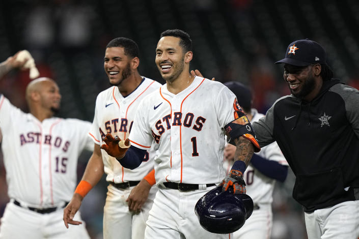 Houston Astros' Carlos Correa (1) celebrates with teammates after hitting a game-winning RBI ground-rule double against the Seattle Mariners during the 10th inning of a baseball game Tuesday, Sept. 7, 2021, in Houston. The Astros won 5-4 in 10 innings. (AP Photo/David J. Phillip)