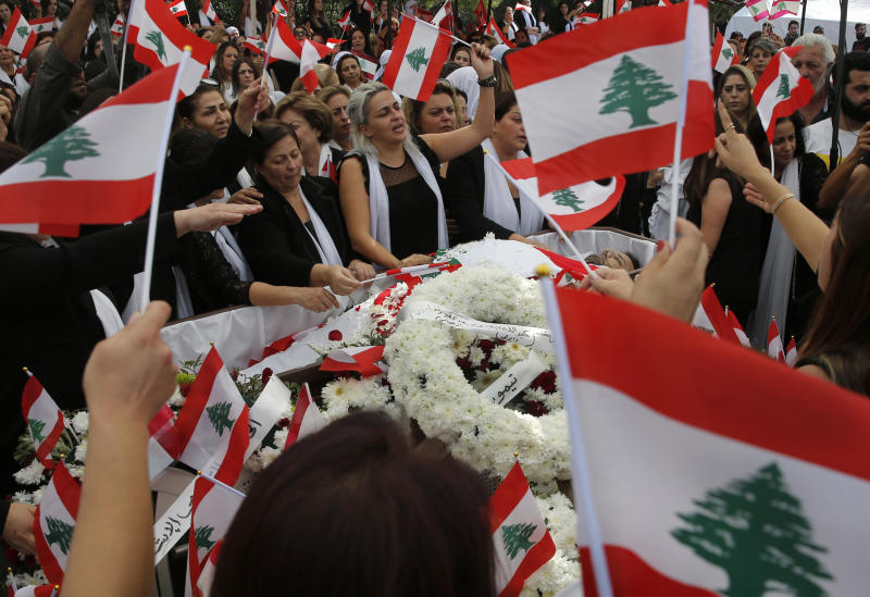 Lara, center, the wife of Alaa Abou Fakher, a man killed by a Lebanese soldier on Tuesday night protests in southern of Beirut, mourns with other relatives as they wave Lebanese flags over his body, during his funeral in Choueifat neighborhood, Lebanon, Thursday, Nov. 14, 2019. For nearly a month, the popular protests engulfing Lebanon have been startlingly peaceful. But the death of the 38-year-old father by a soldier, the first such fatality in the unrest, points to the dangerous, dark turn the country could be heading into. (AP Photo/Hussein Malla)