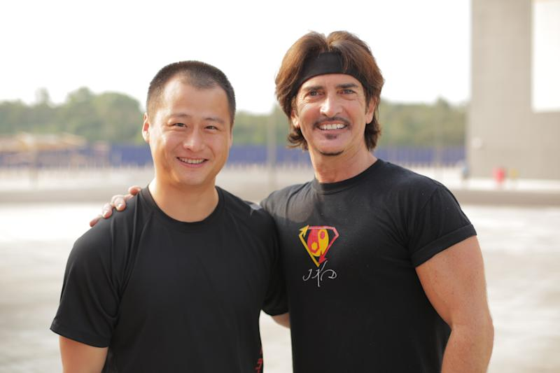 "In this photo taken on Friday, March 7, 2014, provided by Brian Ho, stunt man Ju Kun, left, poses with John Fusco, creator of the show ""Marco Polo"" on the back lot of the new Pinewood Studios in Johor Bahru, Malaysia. Ju Kun, whose credits include the acclaimed martial arts epic ""The Grandmaster,"" was among the passengers on the Malaysia Airlines plane that disappeared early Saturday, March 8, 2014. Ju Kun was scheduled to work on the series pilot for ""Marco Polo,"" a joint Weinstein Co. and Netflix production, at the studio in Malaysia before he boarded the flight to return home to Beijing. (AP Photo/Brian Ho) NO SALES, NO ARCHIVES, MANDATORY CREDIT, ONE TIME USE ONLY"