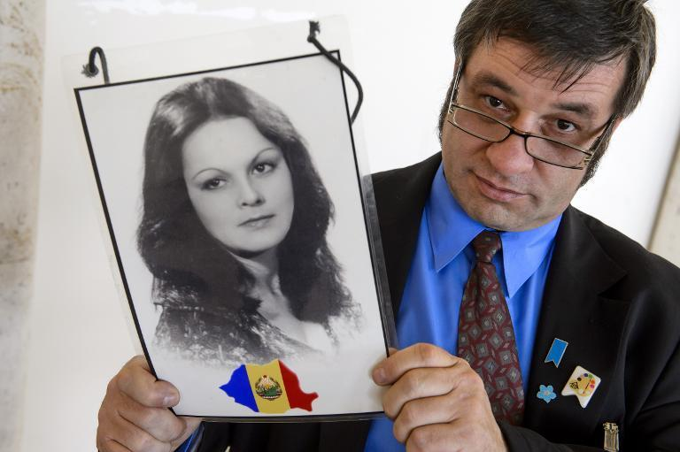 Romanian Gabriel Bumbea poses with a portrait of his sister Doina on the sideline of a session of the UN Human Rights Council on North Korea on March 17, 2014 in Geneva