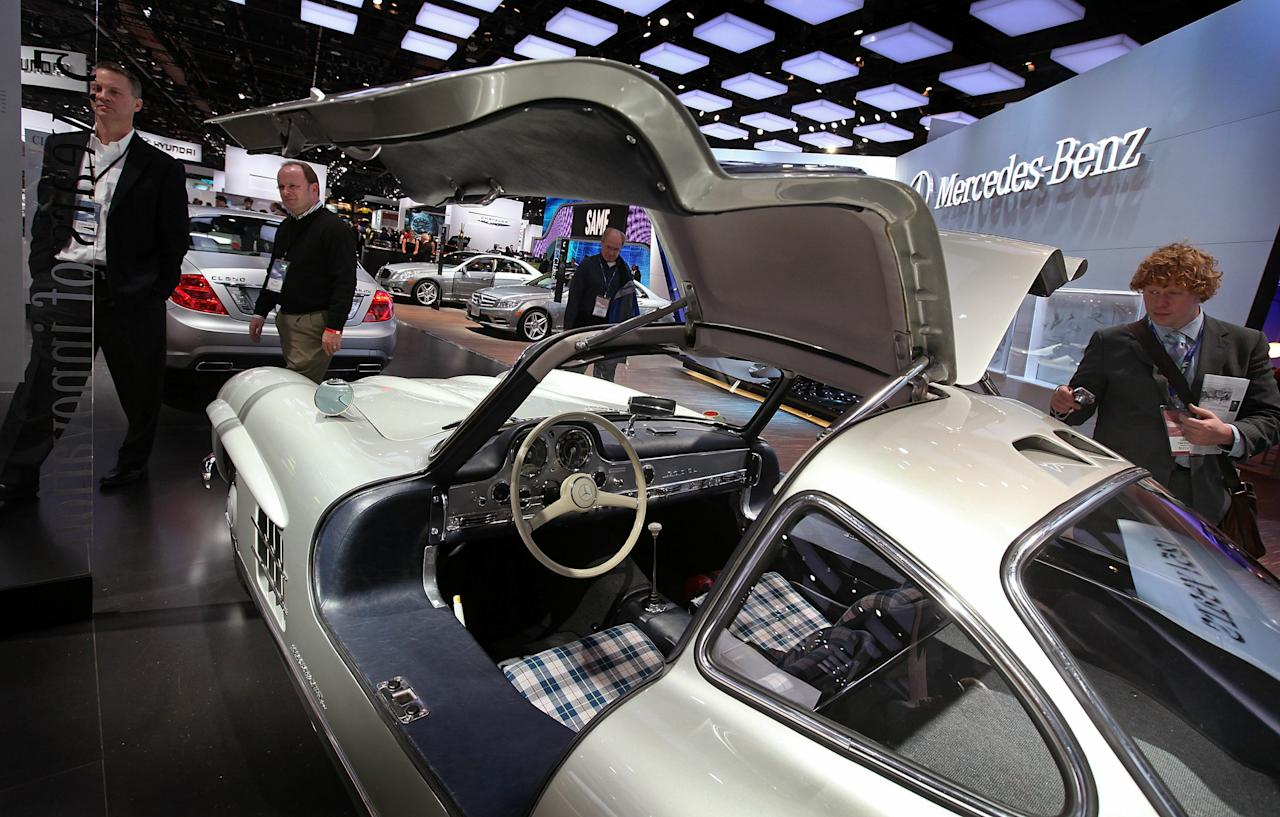 DETROIT, MI - JANUARY 11:  Journalists look over a 1954 Mercedes-Benz 300SL on display during the press preview of the North American International Auto Show at the Cobo Center on January 11, 2011 in Detroit, Michigan. The show is currently opened only for media previews and opens to the general public January 15-23.  (Photo by Scott Olson/Getty Images)
