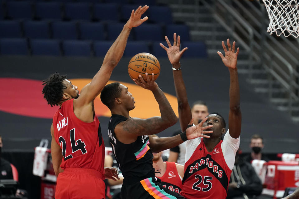 San Antonio Spurs guard Lonnie Walker IV (1) shoots between Toronto Raptors center Khem Birch (24) and forward Chris Boucher (25) during the second half of an NBA basketball game Wednesday, April 14, 2021, in Tampa, Fla. (AP Photo/Chris O'Meara)