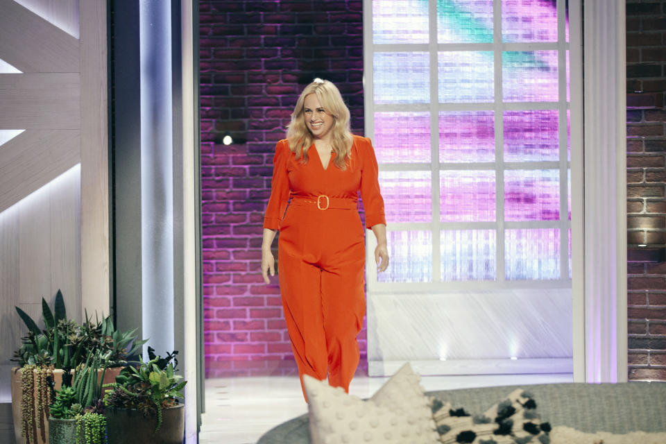 Rebel Wilson wearing a bright orange jumpsuit on set of THE KELLY CLARKSON SHOW Episode 4101 on February 12 2021