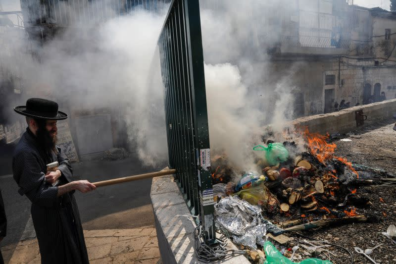 An Ultra-Orthodox Jewish man burns leaven in the Mea Shearim neighbourhood of Jerusalem ahead of the Jewish holiday of Passover