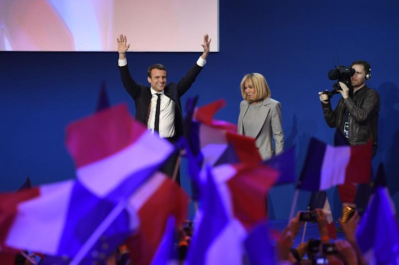Emmanuel Macron and his wife Brigitte Trogneux salute the crowd after projections indicated the 39-year-old centrist led first round voting in France's presidential elections