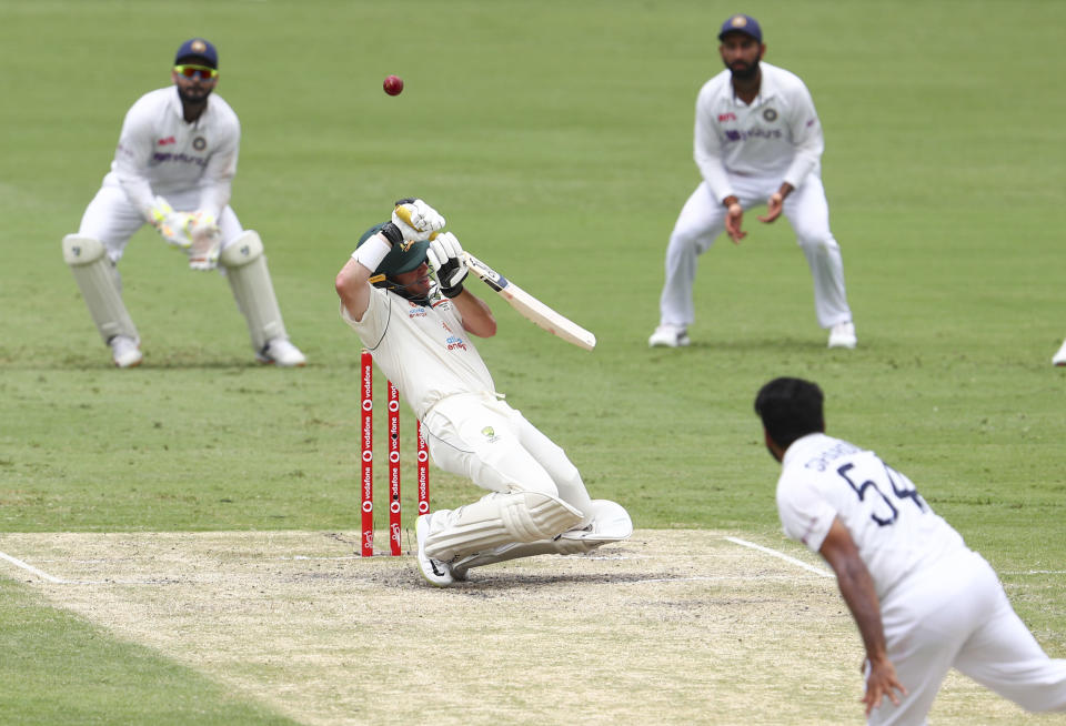 Australia's Marcus Harris hits the ball to be given out during play on day four of the fourth cricket test between India and Australia at the Gabba, Brisbane, Australia, Monday, Jan. 18, 2021. (AP Photo/Tertius Pickard)