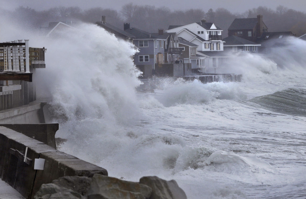 Ocean waves crash over a seawall and into houses along the coast in Scituate, Mass., Thursday, March 7, 2013. A winter storm brought strong winds to coastal areas in the state. (AP Photo/Steven Senne)