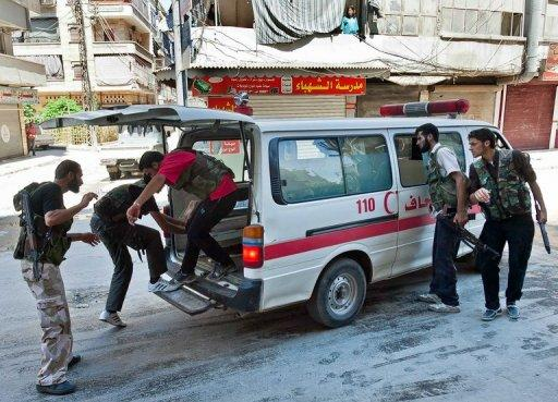 Syrian rebel fighters load a wounded person into an ambulance during clashes with Syrian government forces in Aleppo
