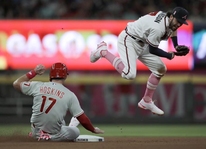 Atlanta Braves' Dansby Swanson, right, hops over Philadelphia Phillies' Rhys Hoskins (17) after completing a double play during the seventh inning of a baseball game Sunday, May 9, 2021, in Atlanta. Phillies' Odubel Herrera was out at first base. (AP Photo/Ben Margot)