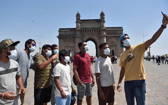 People are seen wearing protective mask as a precaution from Coronavirus at Gateway of India in Mumbai.