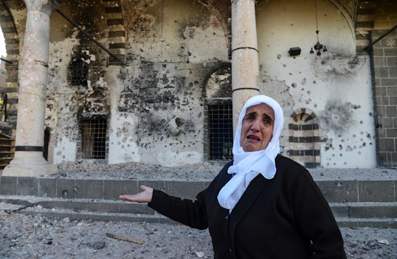 A woman cries in front of a damaged mosque in Sur district in Diyarbakir, on December 11, 2015 (AFP Photo/Ilyas Akengin)