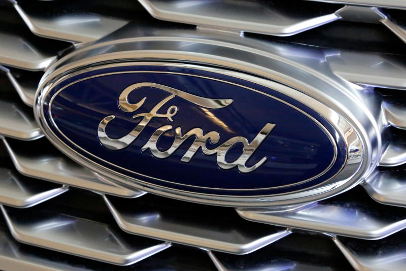 FILE- This Feb. 15, 2018, file photo shows a Ford logo on the grill of a 2018 Ford Explorer on display at the Pittsburgh Auto Show. Ford says it wants to reopen five North American assembly plants in April that were closed due to the threat of coronavirus. The three Detroit automakers suspended production at North American factories March 19, 2020, under pressure from the United Auto Workers union, which had concerns about members working closely at work stations and possibly spreading the virus. (AP Photo/Gene J. Puskar, File)