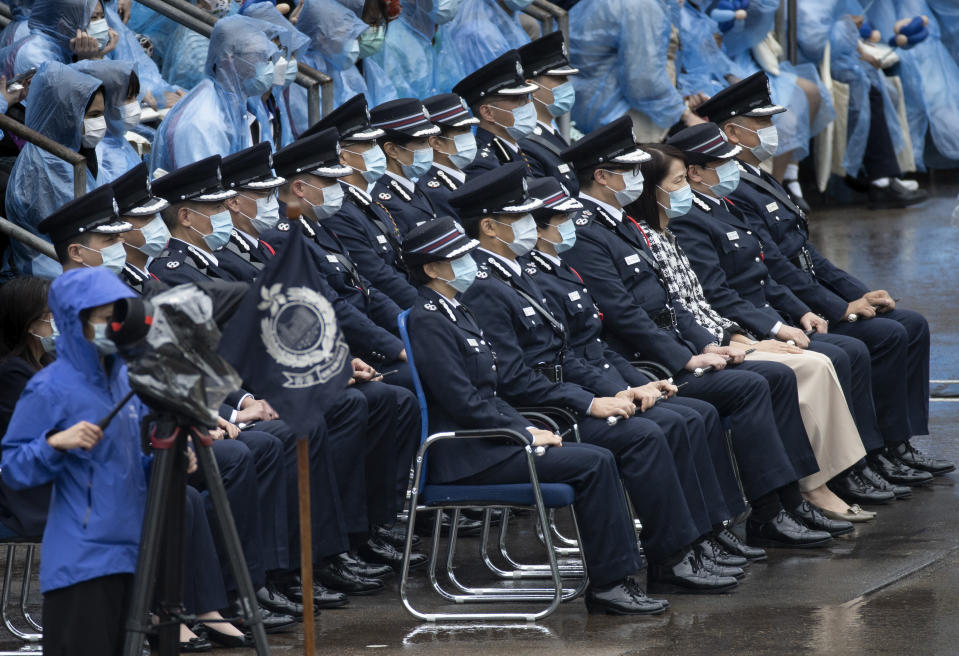 Hong Kong senior police officers including Commissioner of Police, Tang Ping-keung, front row fourth from left, attend a ceremony of the National Security Education Day at a police school in Hong Kong Thursday, April 15, 2021. Authorities marked the event with a police college open house, where police personnel demonstrated the Chinese military's goose step march, replacing British-style foot drills from the time Hong Kong was ruled by the U.K. until the 1997 handover to China. (AP Photo/Vincent Yu)