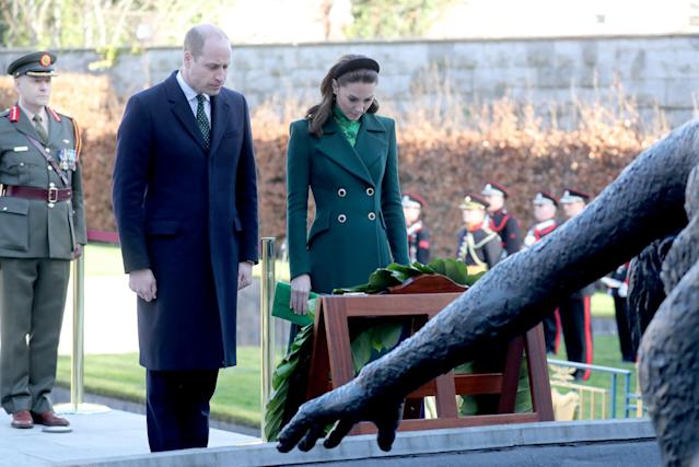 The couple bowed their heads in reflection after laying a wreath which said 'may we never forget the lessons of history'. (Getty Images)
