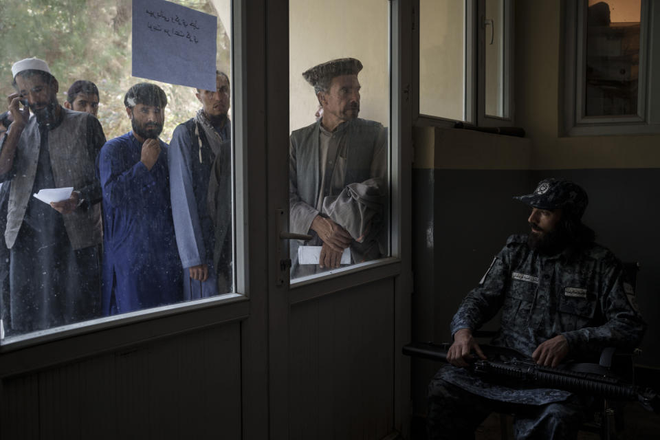 Afghans line up outside a police station in Kabul, Afghanistan, Sunday, Sept. 19, 2021. The Taliban are shifting from being warriors to an urban police force. (AP Photo/Felipe Dana)
