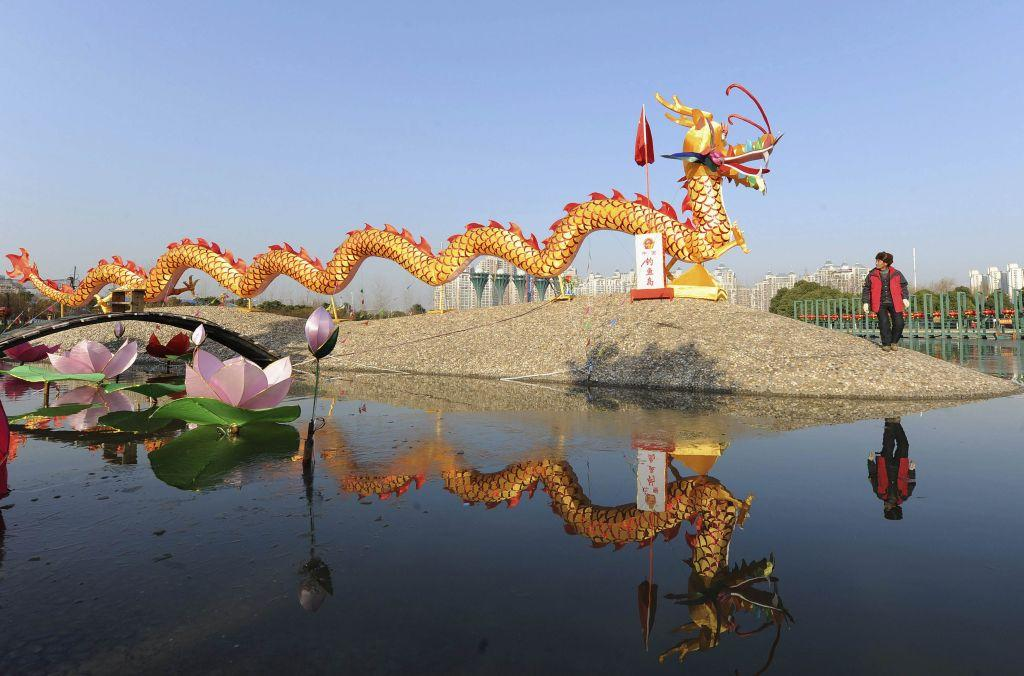 "A worker walks past a dragon-shaped lantern for a lantern festival to celebrate the New Year in Happy Island Park, in Hefei, Anhui province January 1, 2013. The lantern festival will be held from January 1 to February 25, local media said. The Chinese characters on the board in front of the lantern read, ""Diaoyu Islands"", referring to the disputed islands called the Diaoyu in Chinese and the Senkaku by Japan."