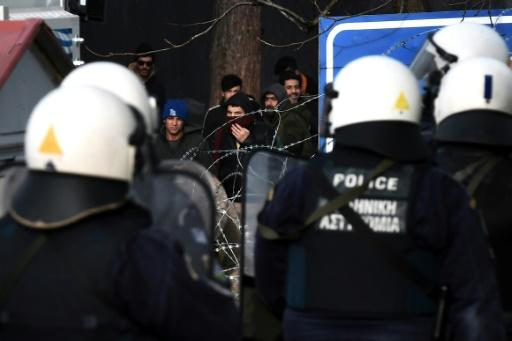 Greek riot police officers watch migrants acrss the barbed wire border