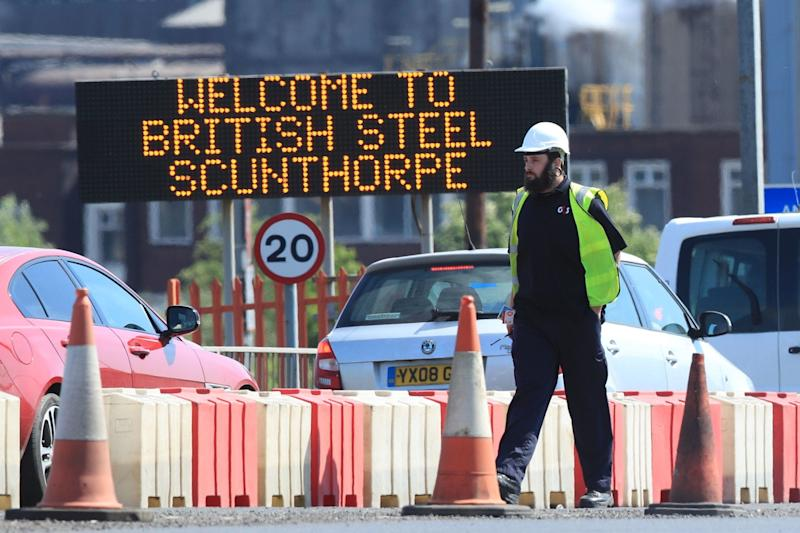 A worker at the entrance to the steelworks plant in Scunthorpe: PA