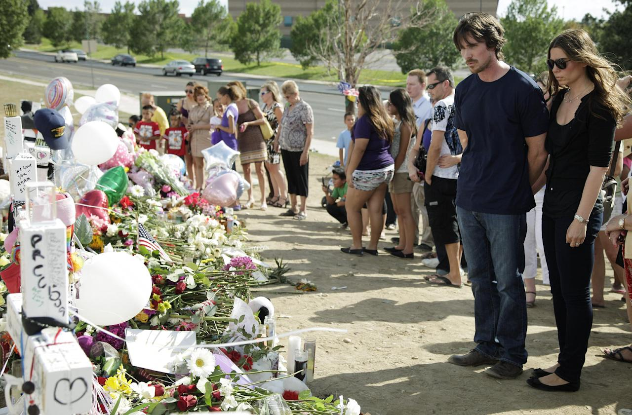 """Actor Christian Bale and his wife Sibi Blazic visit a memorial to the victims of Friday's mass shooting, Tuesday, July 24, 2012, in Aurora, Colo. Twelve people were killed when a gunman opened fire during a late-night showing of the movie """"The Dark Knight Rises,"""" which stars Bale as Batman. (AP Photo/Ted S. Warren)"""