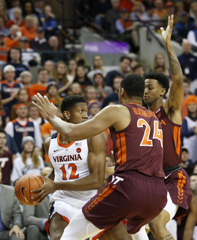 Virginia Tech forward Kerry Blackshear Jr. (24) and Virginia Tech guard Nickeil Alexander-Walker, right, press Virginia guard De'Andre Hunter (12) during the first half of an NCAA college basketball game in Charlottesville, Va., Tuesday, Jan. 15, 2019. (AP Photo/Steve Helber)