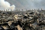 Japan Self Defence troops walking through devastation to search for missing people in the town of Otsuchi on March 13, 2011