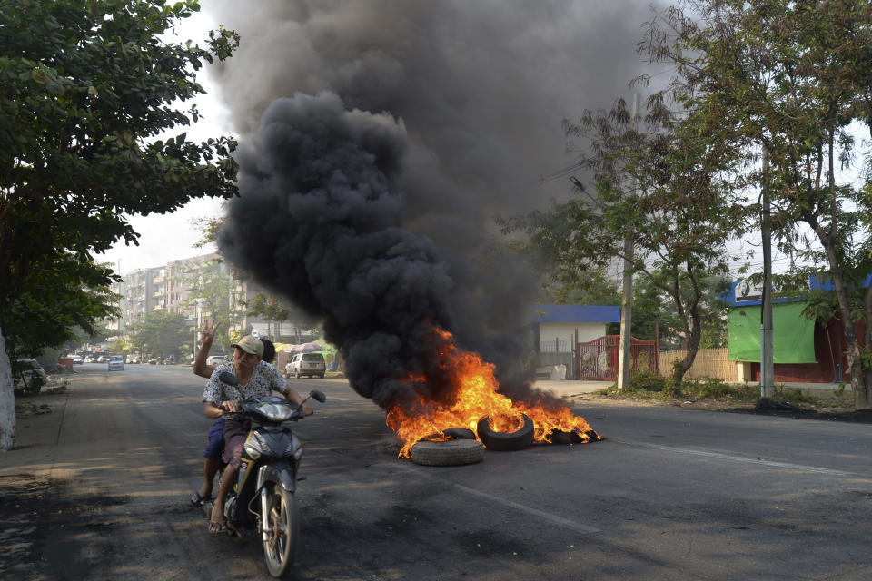 """Anti-coup protesters pass burning tires in Yangon, Myanmar on Thursday March 24, 2021. Protesters against last month's military takeover in Myanmar returned to the streets in large numbers Thursday, a day after staging a """"silence strike"""" in which people were urged to stay home and businesses to close for the day. (AP Photo)"""