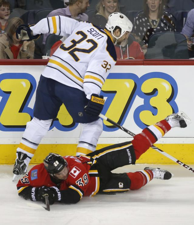 Buffalo Sabres' John Scott (32) dumps Calgary Flames' TJ Galiardi to the ice during first period NHL hockey action in Calgary, Alberta, on Tuesday March 18, 2014. (AP Photo/The Canadian Press, Jeff McIntosh)