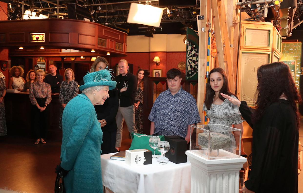 Britain's Queen Elizabeth II meets actors and members of the production team as she visits the set of the long running television series Coronation Street in Manchester, northwest England on July 8, 2021. (Photo by Scott Heppell / POOL / AFP) (Photo by SCOTT HEPPELL/POOL/AFP via Getty Images)